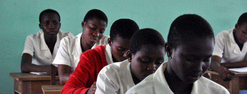 Schülerinnen im Unterricht vor gründer Wand